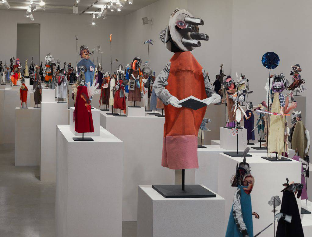 This installation is composed of 365 puppet-like figurines made of bits of paper and fabric and mounted on metal rods. They are displayed on white blocks arranged to form a long procession.