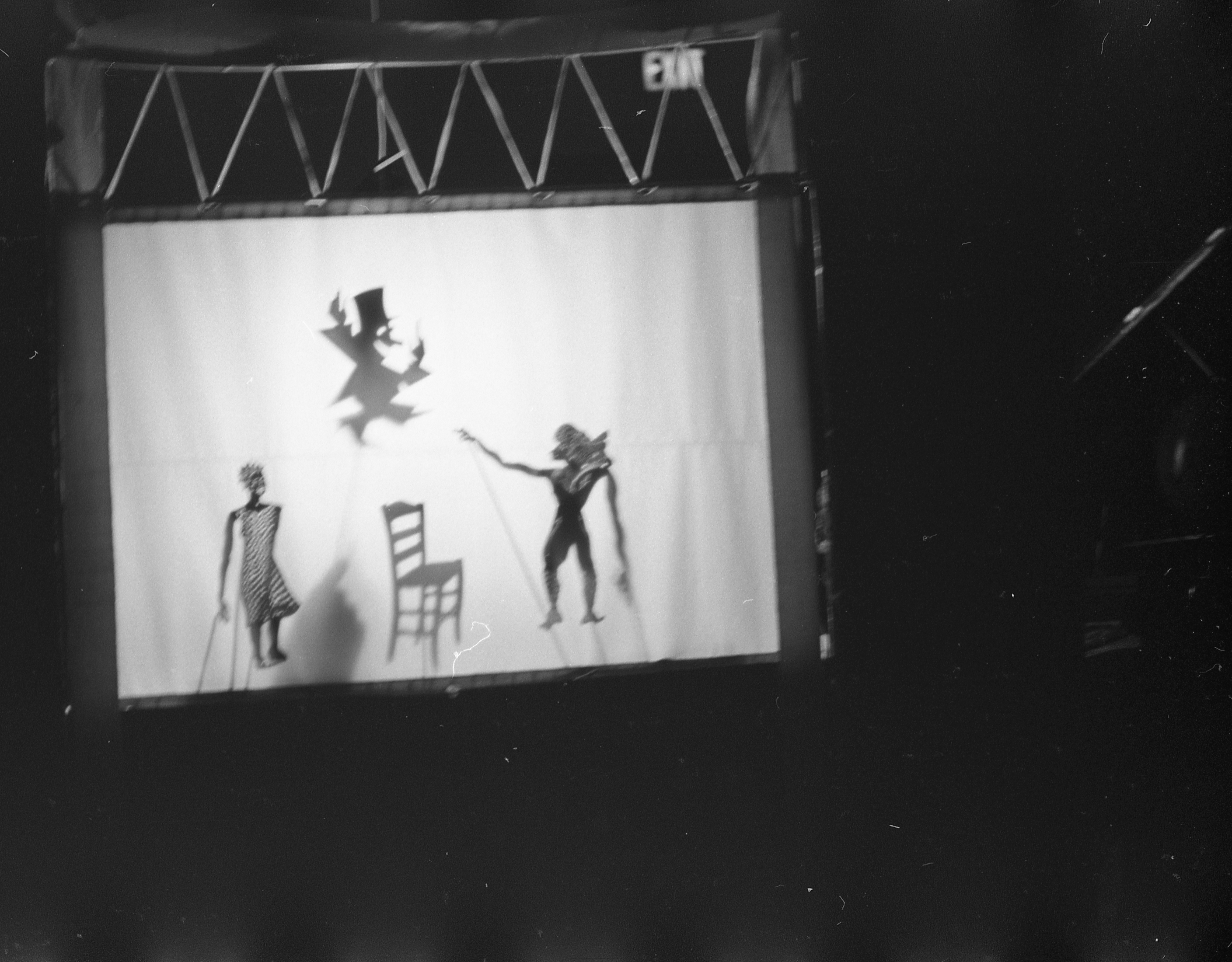 The upper left area of this otherwise dark photograph shows a white screen with the shadows of three stick puppets – one female and two male. They are acting out a scene around a chair.