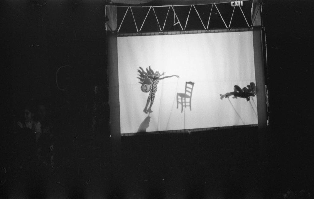 This otherwise dark photograph shows a white screen with the shadows of two stick puppets – a winged figure and a reclining woman – with a chair between them.