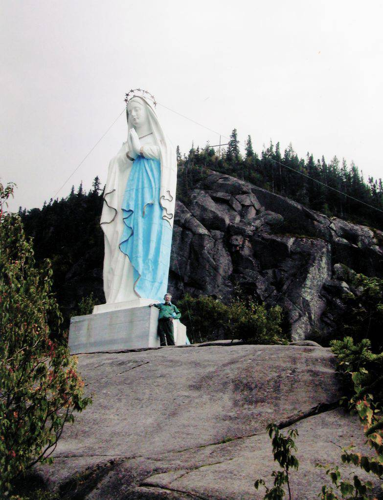 This white and blue statue represents the Virgin Mary standing with her hands joined in prayer and her head slightly bowed. She is haloed with a crown of stars and stands in the open, on a peak of an evergreen-covered cape.