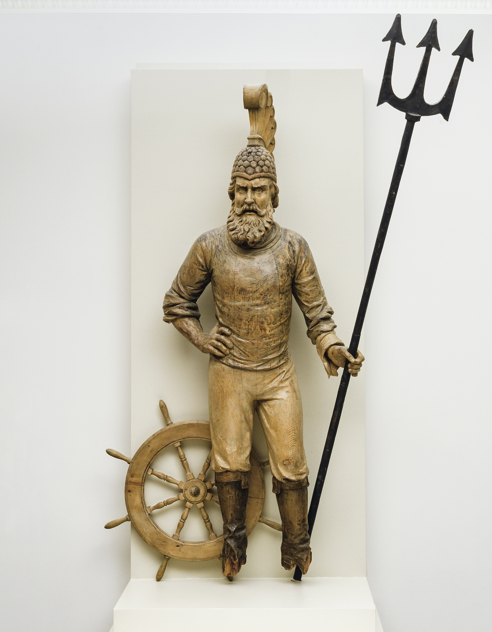 This gilded statue represents a bearded man wearing a crested warrior's helmet. The figure is holding a long trident in his left hand. A ship's wheel stands behind his right leg.