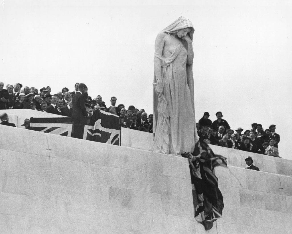This black-and-white photograph shows a crowd of people on a white platform. A man seen in profile stands at the forefront of the crowd, near a Union Jack flag. In front of him is a colossal statue of a woman draped in a cloak. Her covered head is bowed, and her expression conveys sadness.