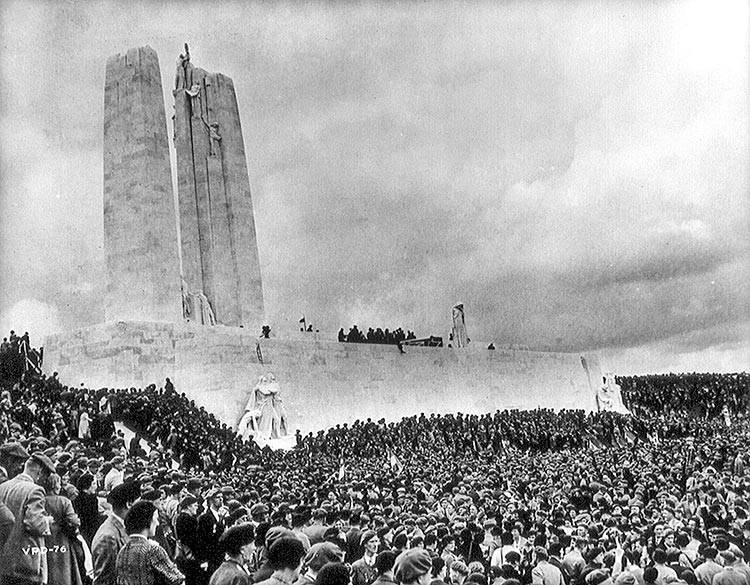 This black-and-white photo shows a crowd of people around an immense monument composed of two pillars on a rectangular base. A number of smaller allegorical sculptures adorn the monument.