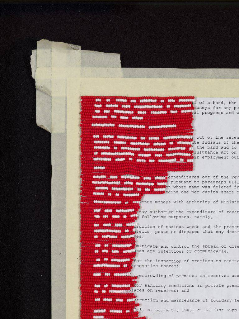 This photo shows a piece of fabric the size of standard letter paper. Part of the cloth is beaded in red and white. The white beads replace the writing against the background of red beads.