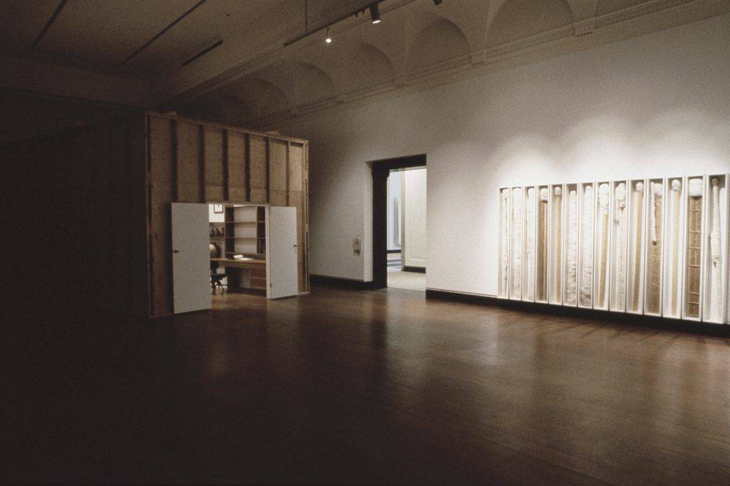 This photo shows an exhibition gallery. At the left is a room made of wooden planks. At the right, rectangular, white, glass-fronted boxes stand side by side against a white wall. The boxes contain wooden sticks wrapped in white string.