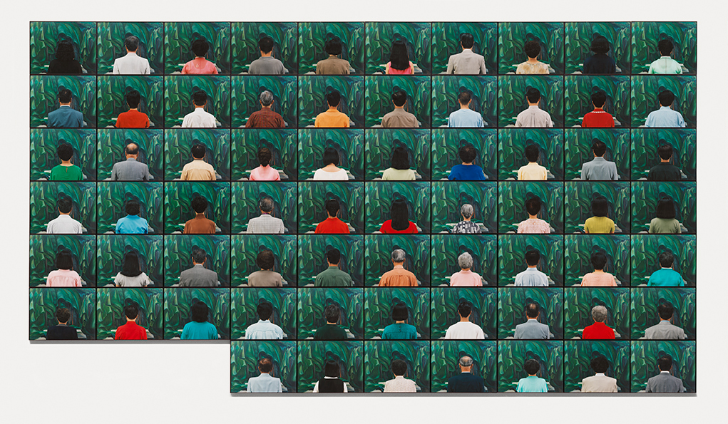 This picture shows sixty-seven photographs of people of Korean descent from behind looking at a painted landscape.