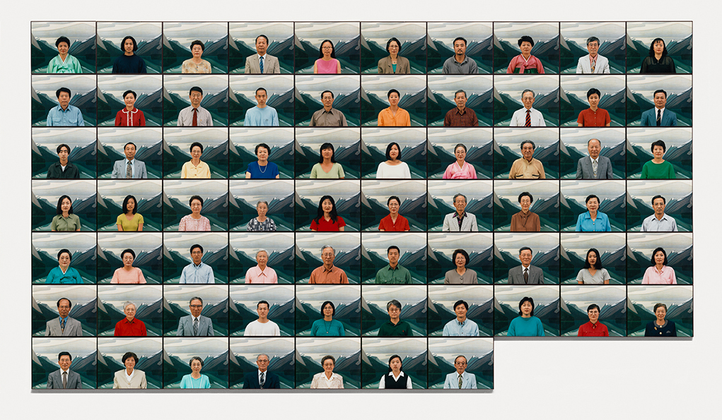 This picture shows sixty-seven photographs of people of Korean descent full-face in front of a painting of mountains.