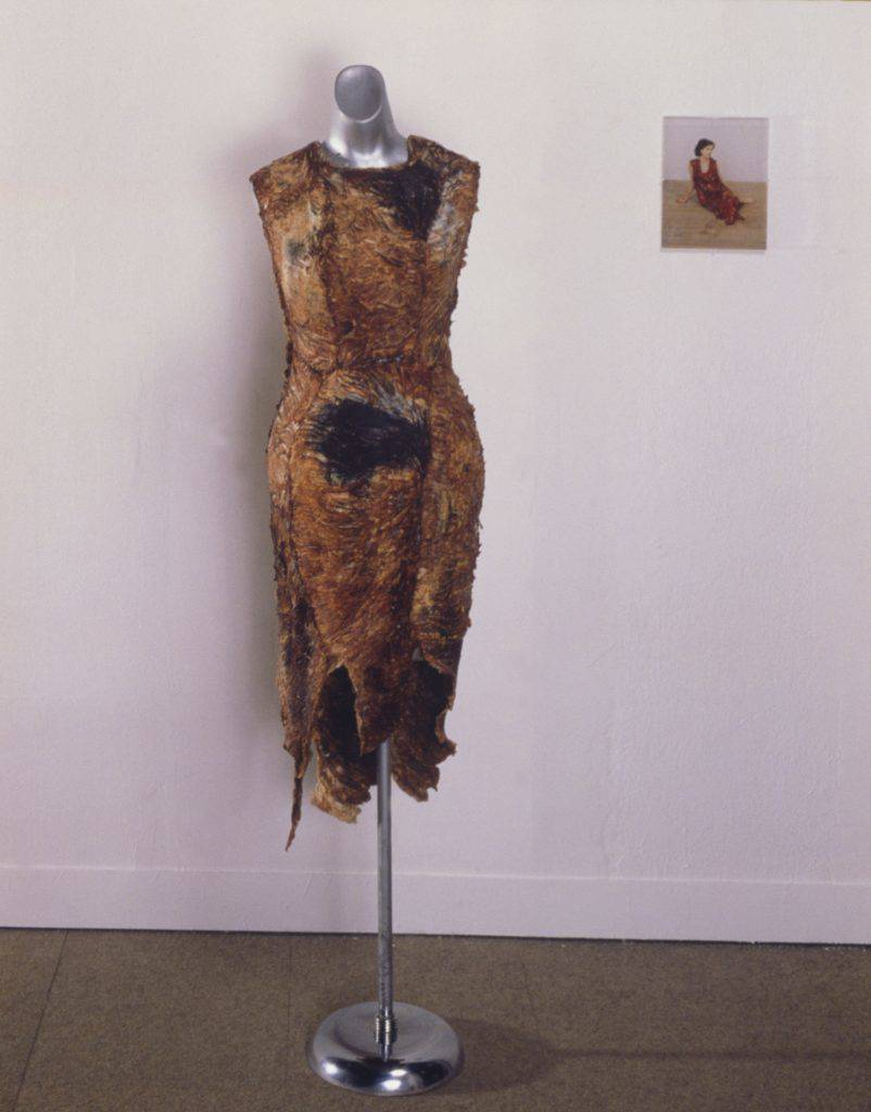 This photograph shows a dress made of slabs of raw beef stitched together hangs on a dressmaker's dummy. The decaying flesh has shrivelled and turned brown.