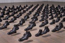 Pairs of military boots arranged in rows are suspended on black strings. The right-foot boots, raised slightly off the floor, create the impression of troops marching.