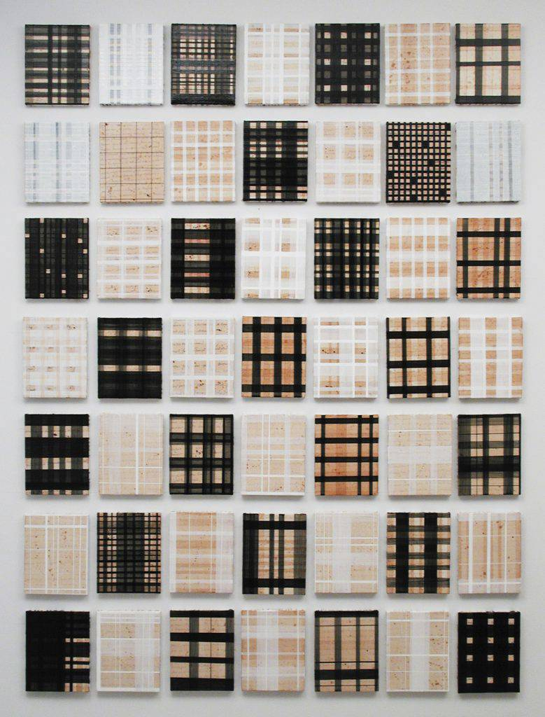 This work is composed of 49 small painting mounted on a wall in a way that suggests a series of woven placemats. On each painting are handwritten words overlaid with spots and checkered motifs beige, white and black.
