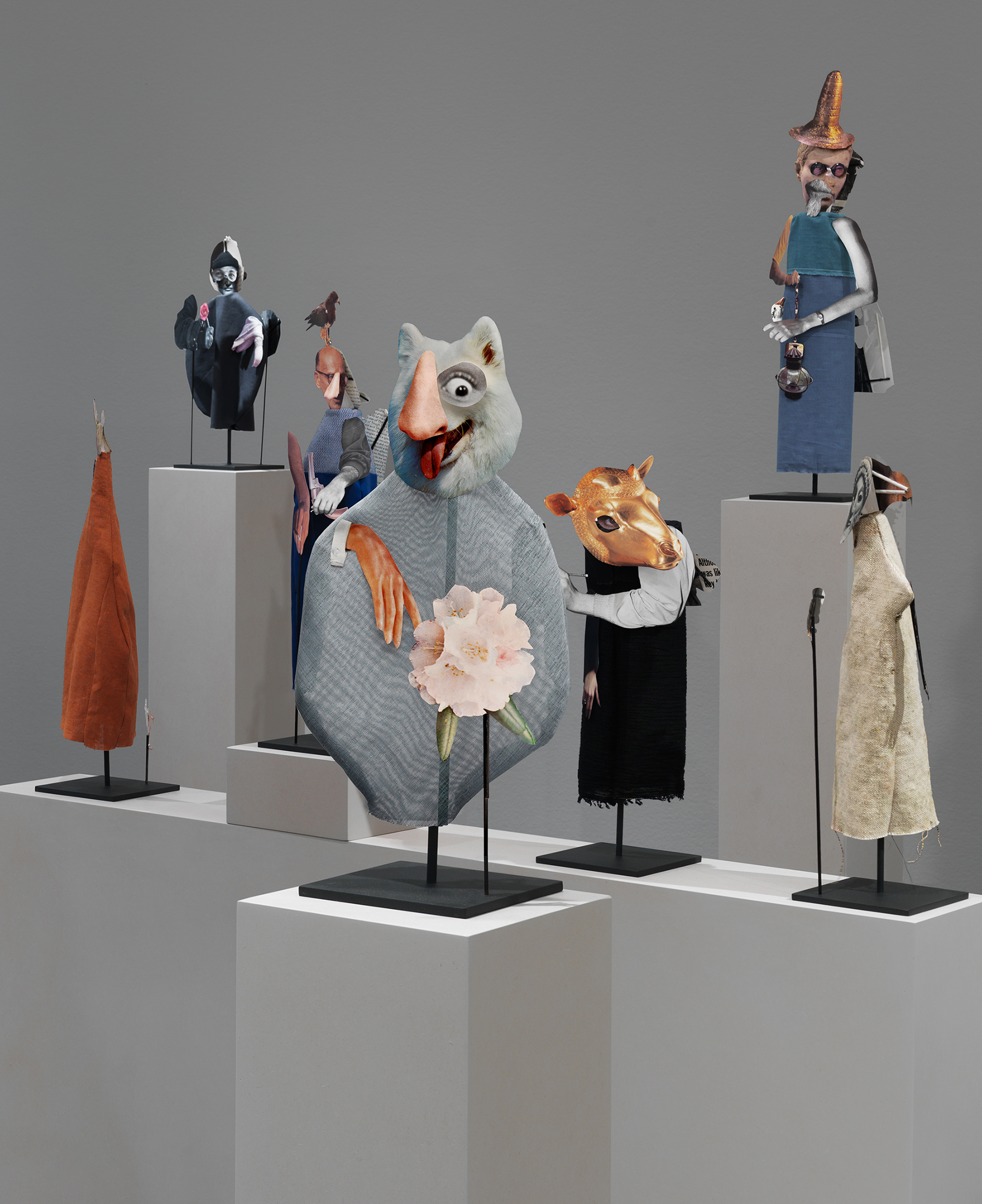 This photograph shows seven puppet-like puppet-like figurines made of bits of paper and fabric and mounted on metal rods. They are displayed on white blocks arranged to form a long procession.