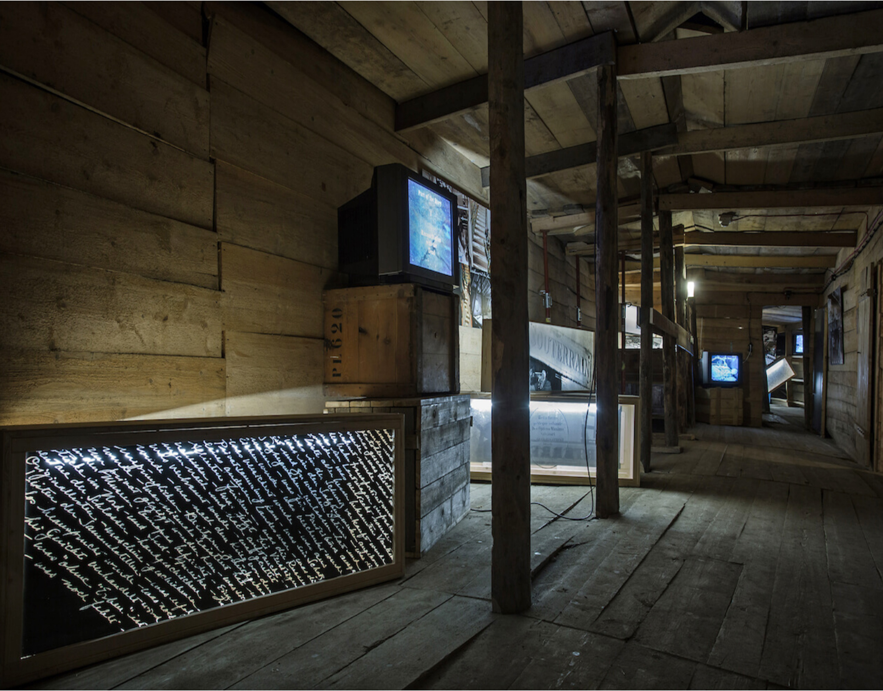 This photo shows a section of the exhibition Body Missing, by Vera Frenkel. Several lightboxes are arranged in a room whose walls and floor are made of wide wooden planks. A video monitor sits on two stacked crates.