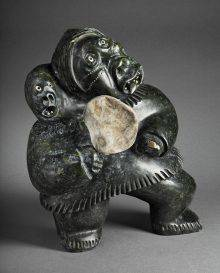 This photo shows a black stone carving of a woman holding a white drum and carrying a child on her back. The two faces are highly expressive.