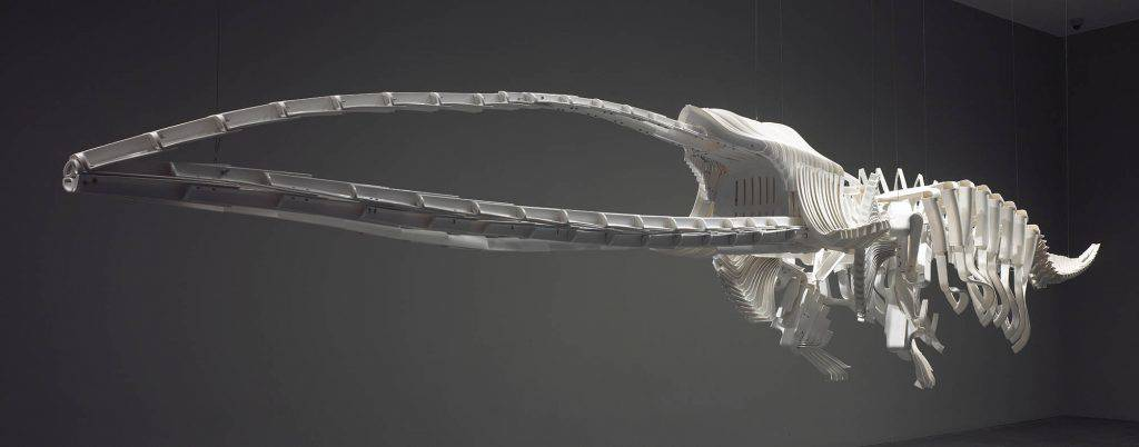 "In a large gallery, the gigantic skeleton of an unidentifiable marine mammal is suspended from the ceiling. The sharp edges of the ""bones"" reveal that they are made of pieces of plastic chairs."