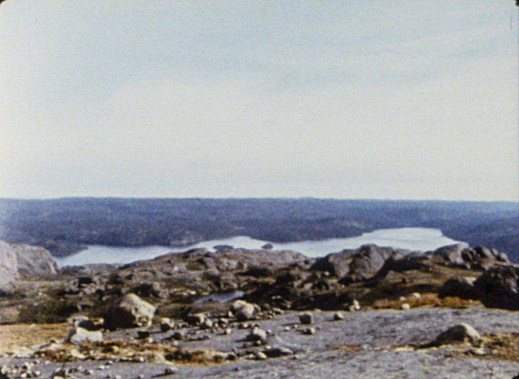 This still frame from the film shows a rocky landscape and a pale blue sky. The horizon line divides the image horizontally in the middle.