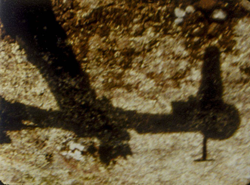 This still frame from the film shows the upside-down shadow of a robotic arm attached to a base.
