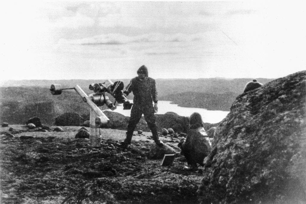 This black-and-white photo shows two people in a rocky landscape. One is crouching and the other is standing next to a camera mounted on a robotic arm attached to a base.