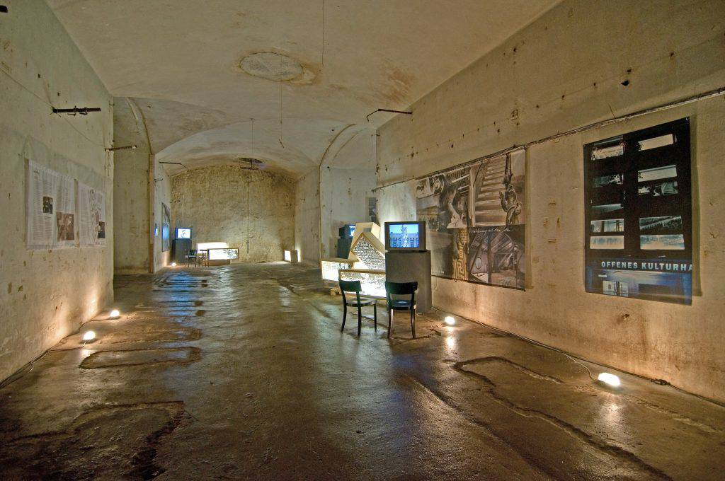 This photo shows a panoramic view of the exhibition Body Missing, by Vera Frenkel. Small clusters of lightboxes are arranged in several places. Photomontages are exposed on the walls. Video monitors sit on top of some of the lightboxes. One image and text are projected onto a wall.