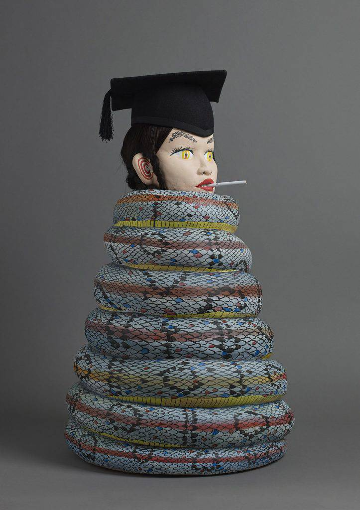 A blue snake with black scale-like checks and red and yellow stripes is coiled in the shape of a cone. It is topped by the head of a heavily made-up girl with reptilian eyes, brown hair and a cigarette in her mouth. She is wearing a graduation cap.